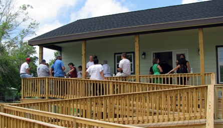 People gather on the front porch; the ramp zigzags down in the foreground.